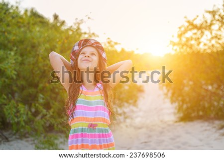 Beautiful little girl in hat on sunset background. - stock photo
