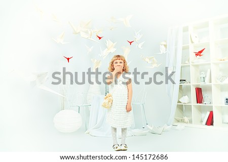 Beautiful little girl in her dream world surrounded with paper birds. - stock photo