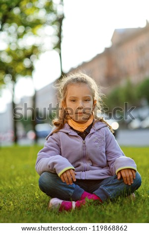 Beautiful little girl in jacket sitting on green lawn, against background of city street.
