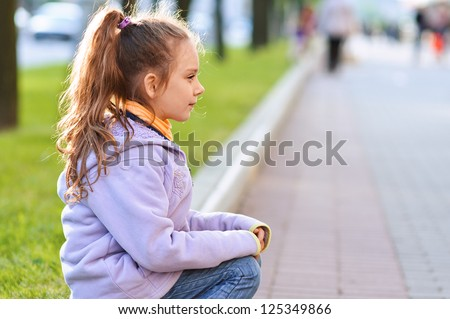 Beautiful little girl in jacket sitting on paving-stone curb profile, against background of city street. - stock photo