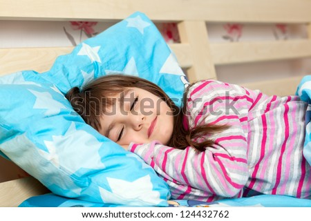 beautiful little girl in pajamas sleep in bed under a blue blanket - stock photo