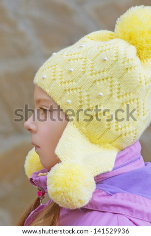 Beautiful little girl in pink jacket and yellow cap close-up in profile against a stone wall. - stock photo