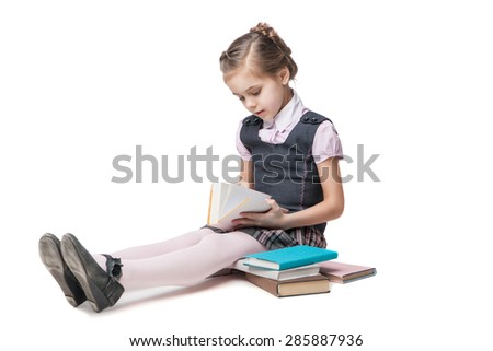 Beautiful little girl in school uniform with books sitting on the floor - stock photo