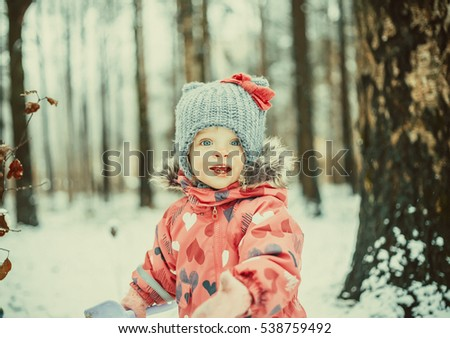 Beautiful little girl in snowy winter park