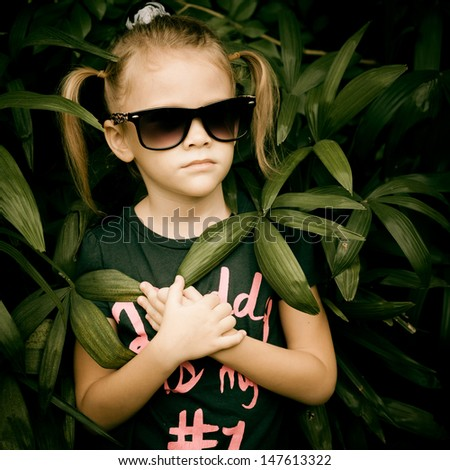 """beautiful little girl in sunglasses and a black T-shirt that says """"Daddy"""" - stock photo"""