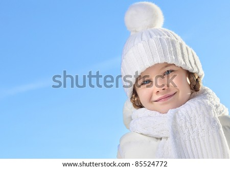beautiful little girl in winter clothing outdoors looking at camera - stock photo