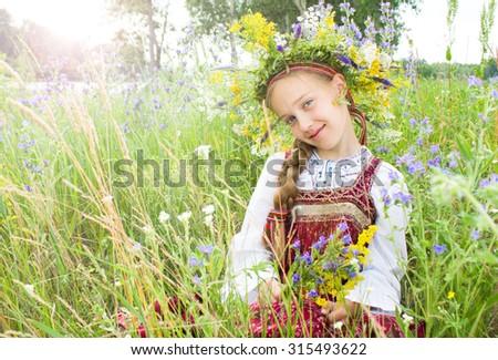 Beautiful little girl in wreath of flowers lay in meadow - stock photo