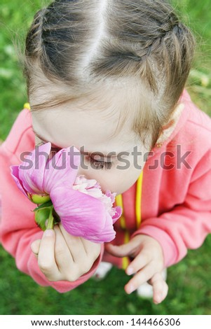 Beautiful little girl inhales the scent of a flower - stock photo