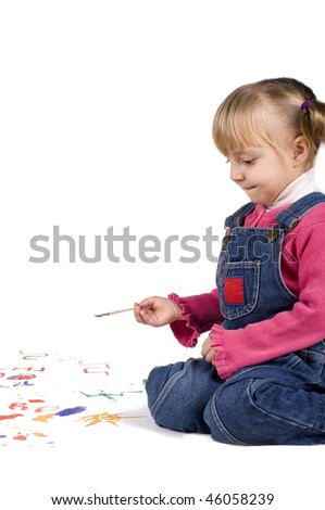 Beautiful little girl is drawing with gouaches on paper