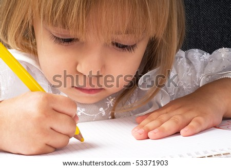 Beautiful little girl is drawing with pencil on paper - stock photo