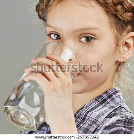 Beautiful little girl is drinking water, on gray background. - stock photo