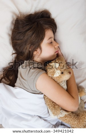 Beautiful little girl is sleeping with her teddy bear.Little girl sleeping  - stock photo