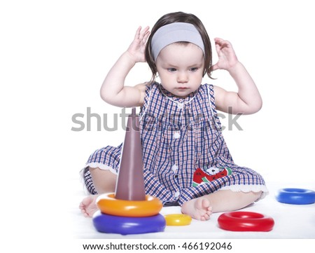 beautiful little girl isolated on a white background playing with pyramid