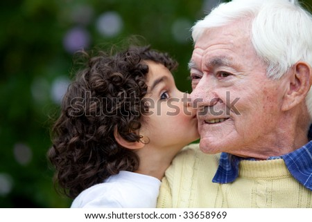 beautiful little girl kissing happily her grandfather - stock photo