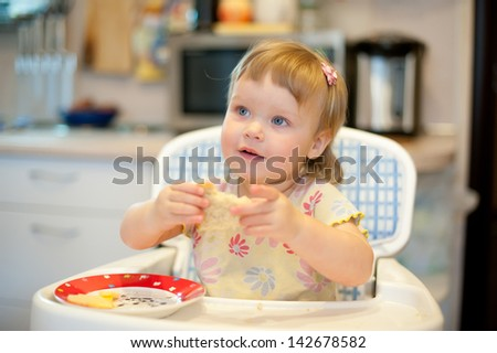 Beautiful little girl laughing in the kitchen.
