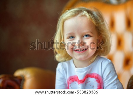 beautiful little girl, laughs and poses on the camera, joyful emotions