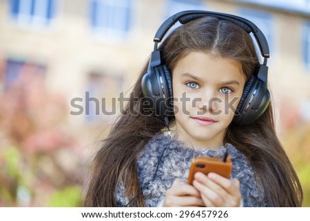 Beautiful little girl listening to music on headphones in autumn park