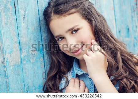 beautiful little girl looking at the camera on a blue background - stock photo