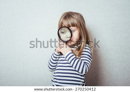 Beautiful little girl looking through a magnifying glass - stock photo