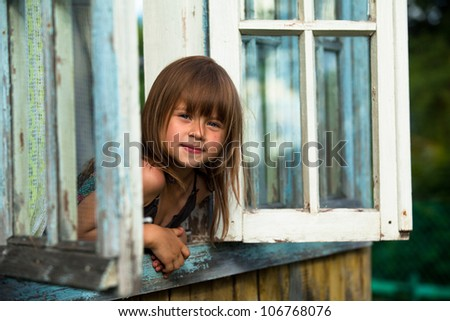 Beautiful little girl looks out the window rural house - stock photo