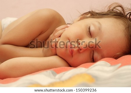 Beautiful little girl lying in bed at home