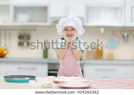 Beautiful little girl making the dough. - stock photo