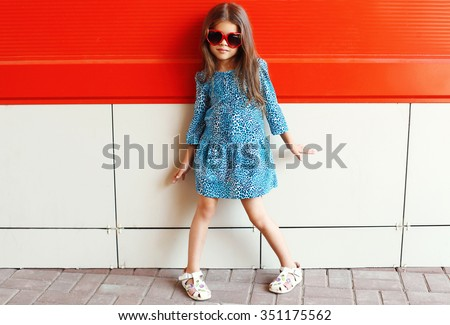 Beautiful little girl model wearing a leopard dress and sunglasses over colorful red background - stock photo