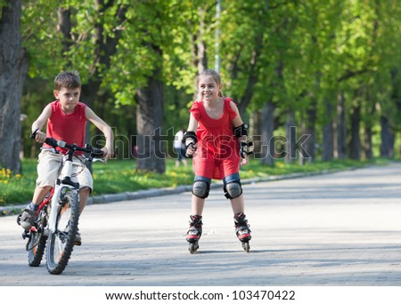 Beautiful little girl on in-line skates smiling and looking at little boy on bicycle in front of her - stock photo