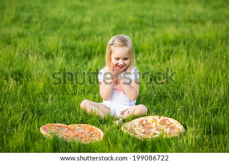 Beautiful little girl on outdoors with pizza
