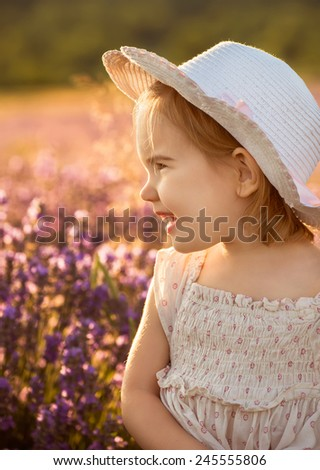 Beautiful little girl on the background of a lavender field at sunset - stock photo