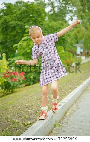 Beautiful little girl oscillates on pavement curb. - stock photo
