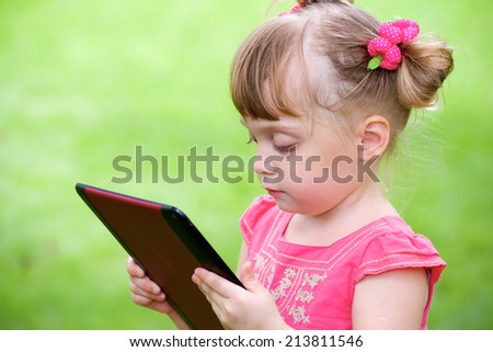 Beautiful little girl outdoor looking on tablet pc on hands - stock photo