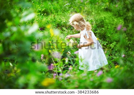 Beautiful little girl picking flowers in a meadow. Summer sunny day, lots of greenery and flowers. Blonde girl in white dress.