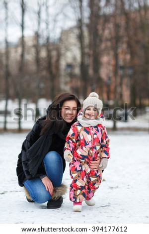Beautiful little girl playing in the park with her mother in winter