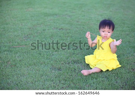 Beautiful little girl playing with grass - stock photo