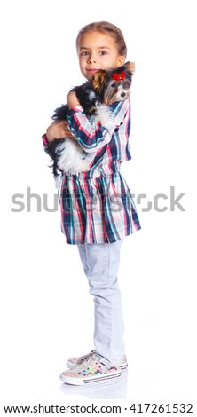 Beautiful little girl playing with her yorkshire terrier. Isolated on the white background