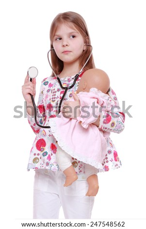 Beautiful little girl playing with toy doll  - stock photo