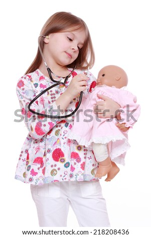 Beautiful little girl playing with toy doll over white - stock photo