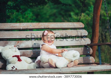 Beautiful little girl playing with toys on a wooden bench in a green park - stock photo