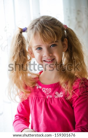 beautiful little girl posing by the window - stock photo
