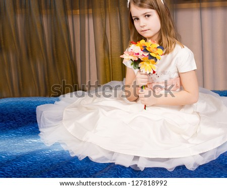 Beautiful little girl posing sitting on the floor on a blue carpet in a tutu with the filmy gauze skirt spread out around her while she holds a bouquet of flowers in her hands - stock photo