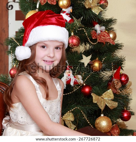 Beautiful little girl reading old book near the christmas tree on Holiday theme/Happy young girl holding vintage book on Education theme - stock photo