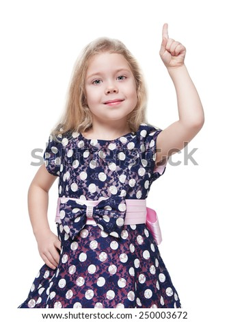 Beautiful little girl showing on something by finger isolated over white background - stock photo