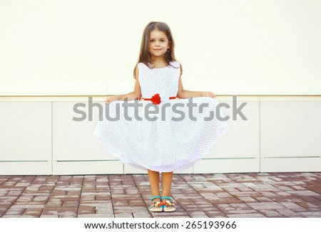 Beautiful little girl shows white dress outdoors against the urban wall - stock photo