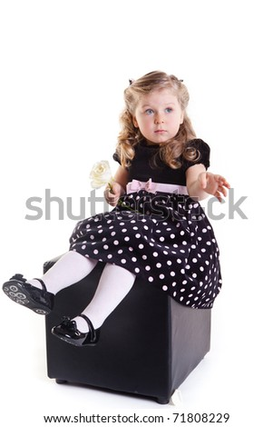 beautiful little girl sitting in black padded stool and holding white rose - stock photo
