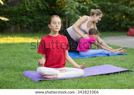 Beautiful little girl sitting in young pose on grass at outdoor lesson - stock photo