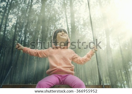 Beautiful little girl sitting on a swing while wearing jacket in the pine forest - stock photo