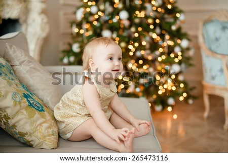 beautiful little girl sitting on the couch, Christmas tree in the background - stock photo