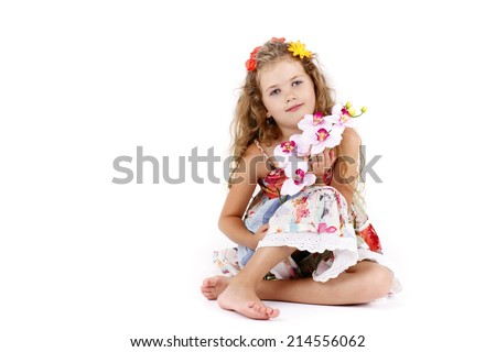 Beautiful little girl sitting on the floor and holding orchid