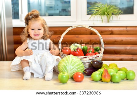 Beautiful little girl sitting surrounded by fresh fruits and vegetables. Kitchen interior. Autumn season. - stock photo
